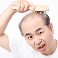 髪をクシでとかす薄毛の男性